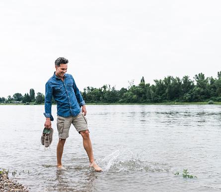 Smiling man splashing water in a river - gettyimageskorea