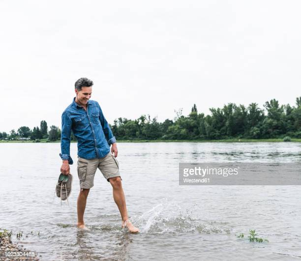 smiling man splashing water in a river - shorts stock pictures, royalty-free photos & images
