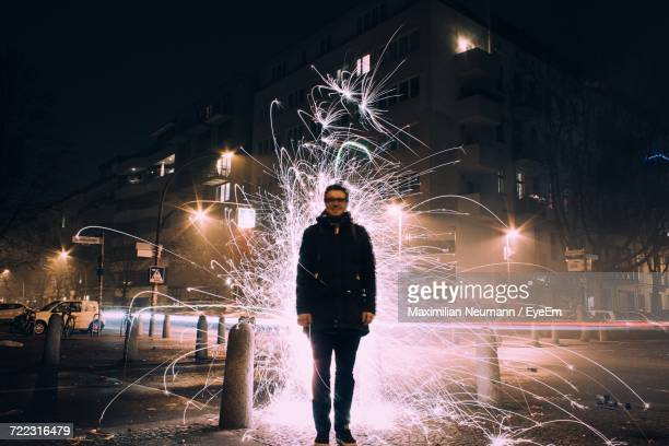 smiling man standing against fire crackers on sidewalk in city at night - glowing stock pictures, royalty-free photos & images