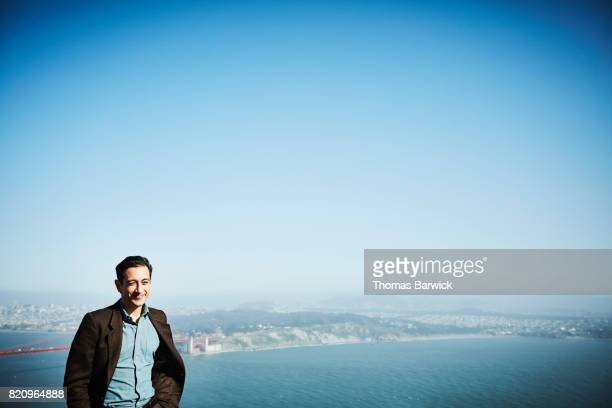 Smiling man standing at vista overlooking San Francisco