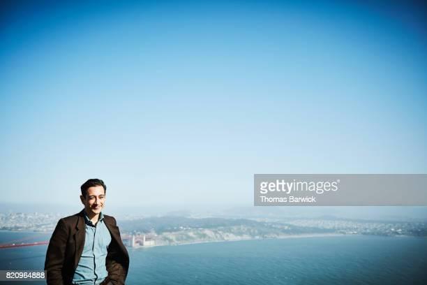 Smiling man standing at vista overlooking San Francisco