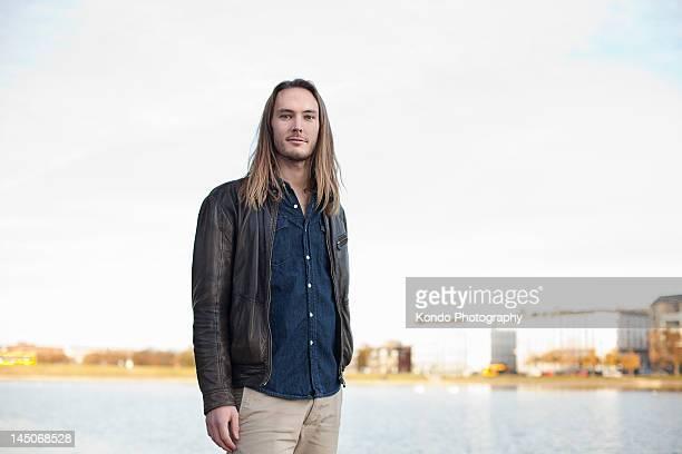 smiling man standing by urban lake - lang fysieke beschrijving stockfoto's en -beelden