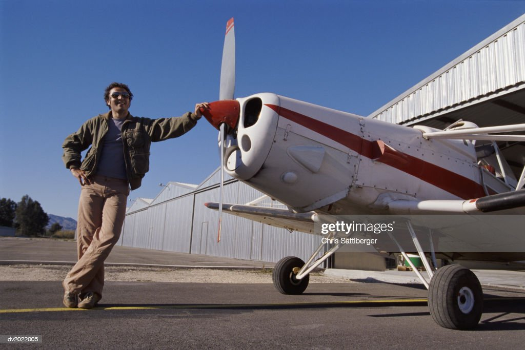 Smiling Man Standing Next to a Monoplane : Stock Photo