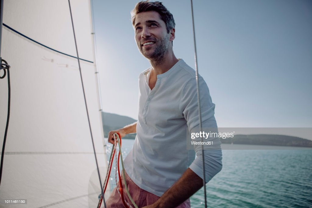 Smiling man standing on a sailing boat : Stock Photo