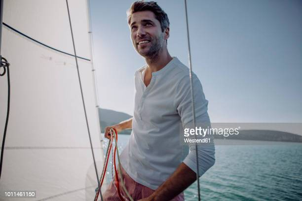 smiling man standing on a sailing boat - segeln stock-fotos und bilder