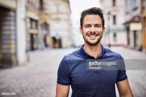 smiling man standing on city street - polo shirt stock pictures, royalty-free photos & images