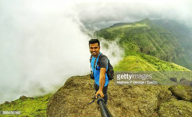 Smiling Man Standing On Cliff Taking Selfie Against Cloudy Mountains