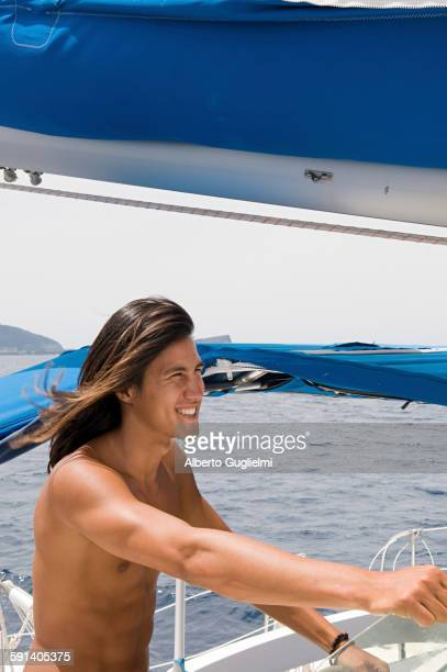 Smiling man standing on sailboat deck