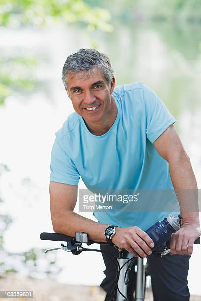 sonriente hombre de pie con bicicleta - cabello castaño fotografías e imágenes de stock