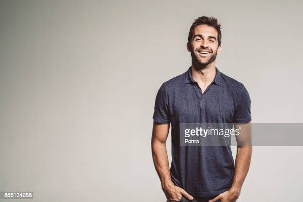 smiling man standing with hands in pockets - three quarter front view stock pictures, royalty-free photos & images