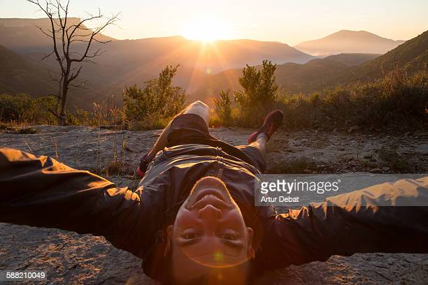 Smiling man taking a selfie laying on the nature