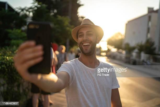 homme de sourire prenant un selfie sur la rue - escapade urbaine photos et images de collection