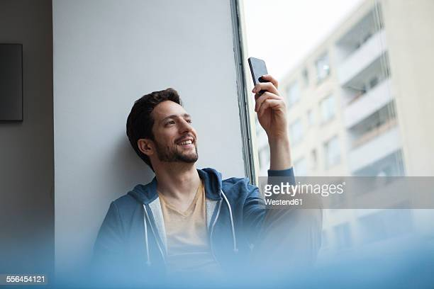 Smiling man taking a selfie with his smartphone