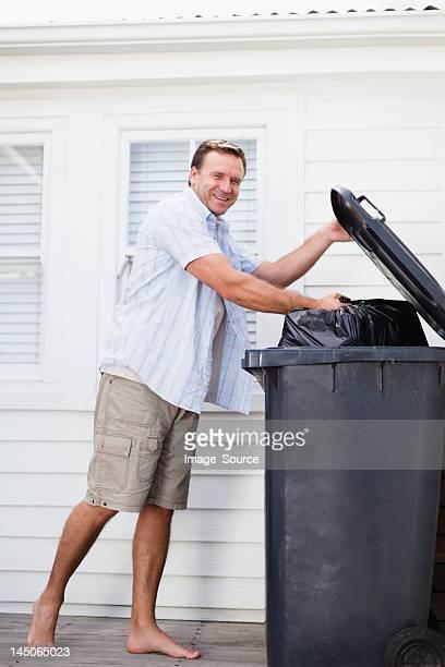 Smiling man taking out garbage