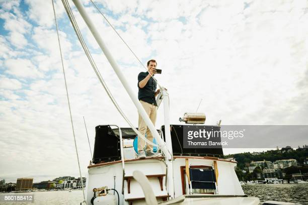 Smiling man taking picture with smartphone from flybridge of boat on summer evening