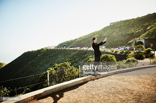 Smiling man taking selfie with smartphone while standing at viewpoint