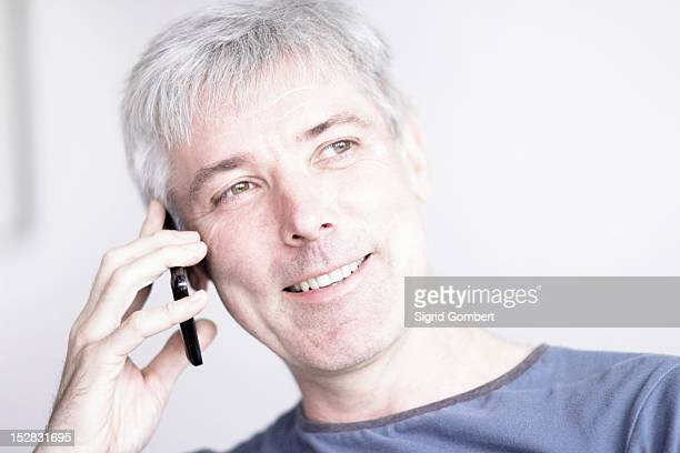 smiling man talking on cell phone - sigrid gombert fotografías e imágenes de stock