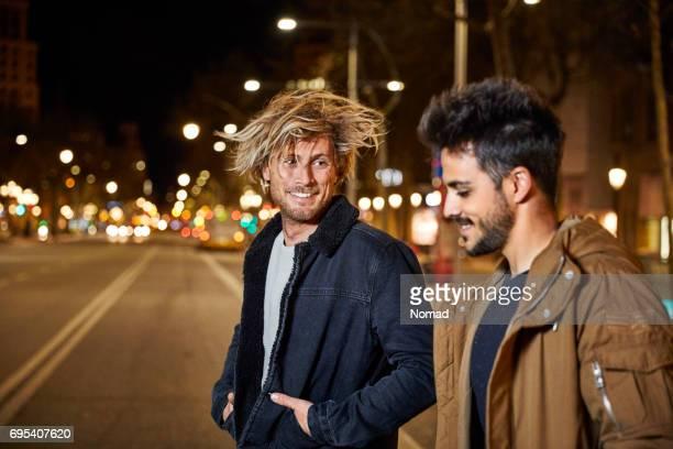 Hombre sonriente hablando con amigo en la calle por la noche