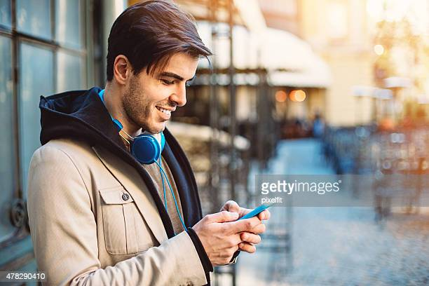 Smiling man text messaging with smart phone