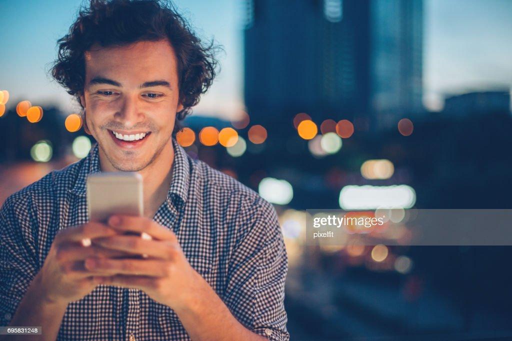 Smiling man texting at night : Stock Photo