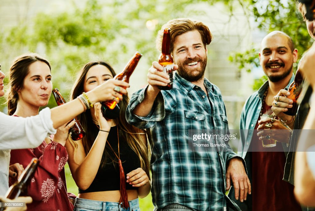 Smiling Man Toasting With Friends During Backyard Party On Summer Evening Stock Photo