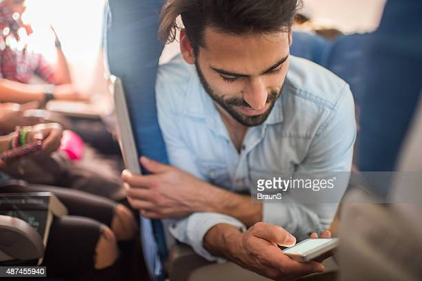 Smiling man travelling by airplane and using smart phone.