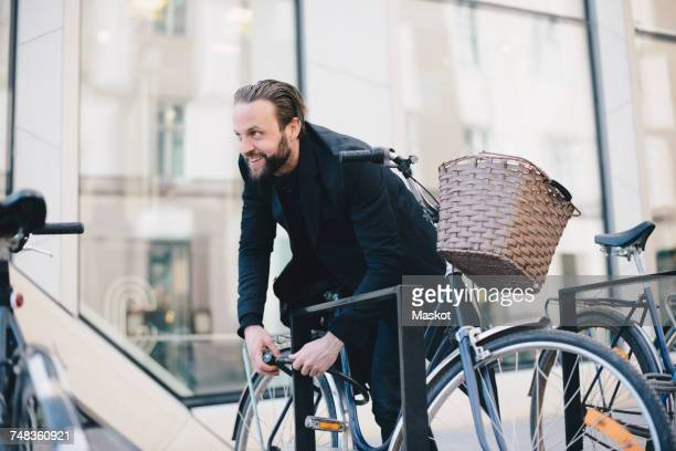 Smiling man unlocking bicycle at rack in city