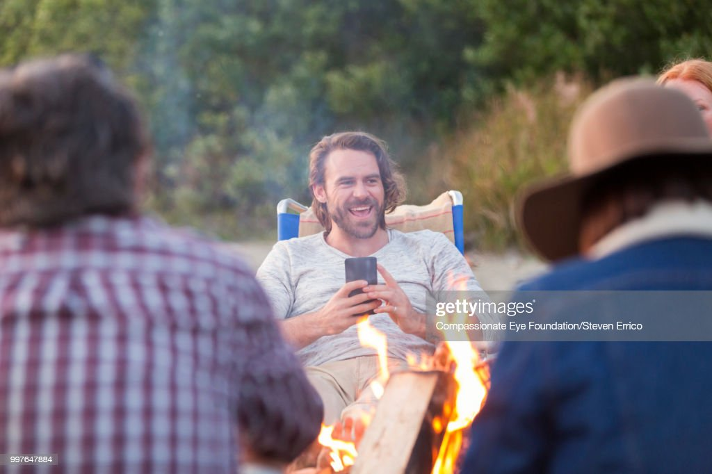 Smiling man using cell phone on beach by camp fire : Stock Photo