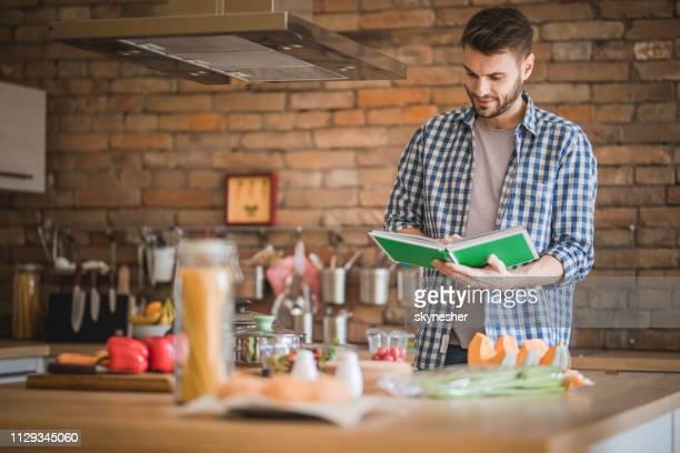 lächelnder mann mit kochbuch für die zubereitung von speisen in der küche. - kochbuch stock-fotos und bilder