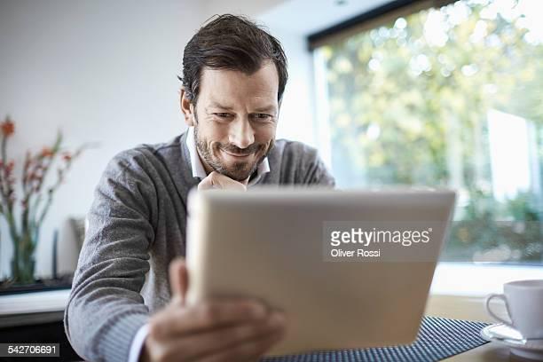 Smiling man using digital tablet at home
