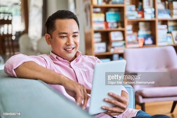 smiling man using digital tablet in living room - malaysia stock pictures, royalty-free photos & images