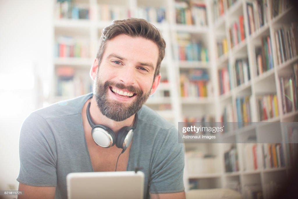 Smiling man using digital tablet in living room : Stock Photo