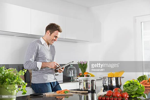 Smiling man using digital tablet in the kitchen