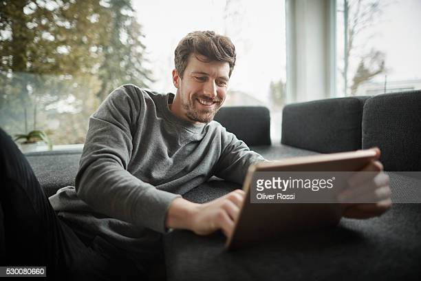 Smiling man using digital tablet on couch