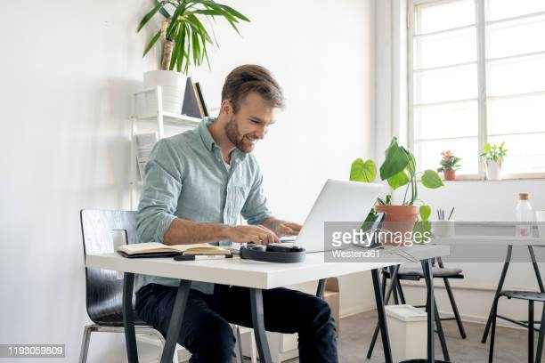 smiling man using laptop at desk in office - working from home stock pictures, royalty-free photos & images