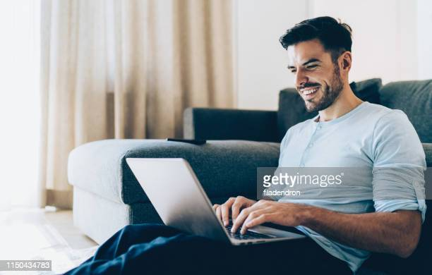 smiling man using laptop - free images stock pictures, royalty-free photos & images