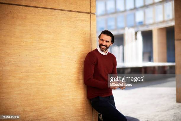 Smiling Man Using Mobile Phone