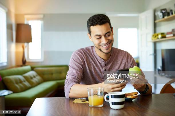 smiling man using mobile phone while holding apple - blackberry fruit stock pictures, royalty-free photos & images