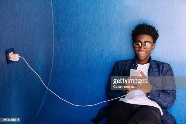smiling man using mobile phone while sitting in library - aufladen stock-fotos und bilder