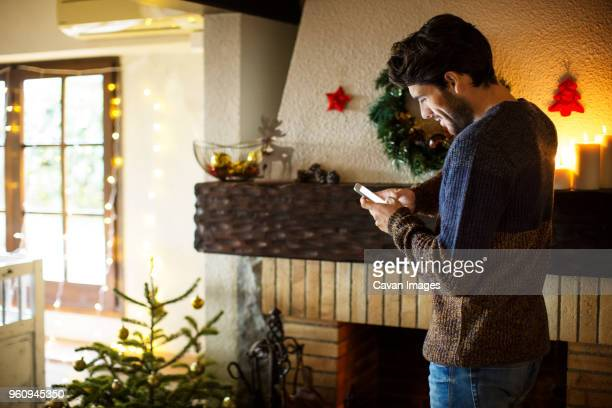 smiling man using smart phone while standing at home during christmas - 男性一人 ストックフォトと画像