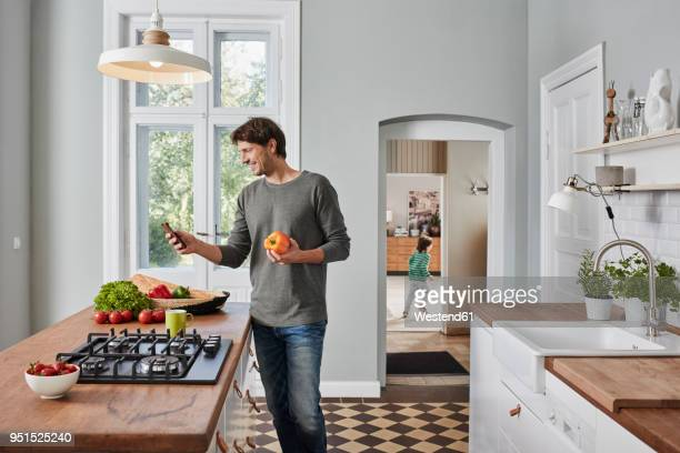 Smiling man using smartphone and holding bell pepper in kitchen