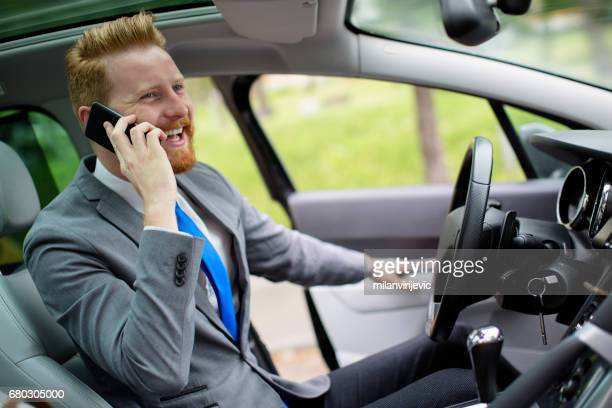 Smiling man using smartphone in the car