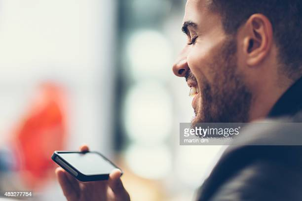 smiling man using smartphone to watch tv - webinar stock photos and pictures