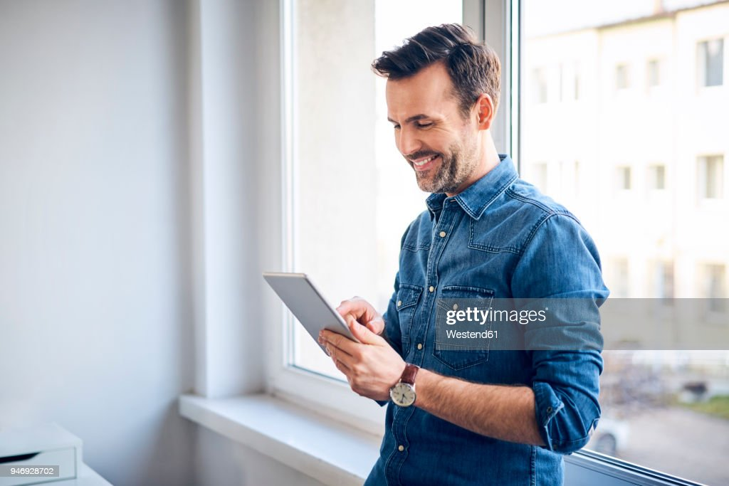 Smiling man using tablet at the window : Stock Photo