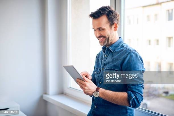 smiling man using tablet at the window - financiën en economie stockfoto's en -beelden