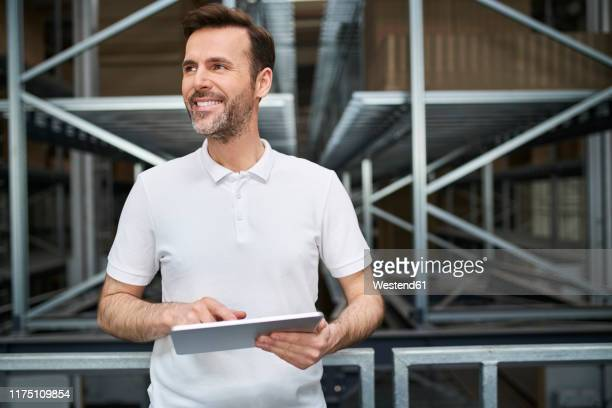 smiling man using tablet in a factory - polo shirt stock pictures, royalty-free photos & images
