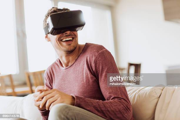smiling man using vr headset - head mounted display stock photos and pictures