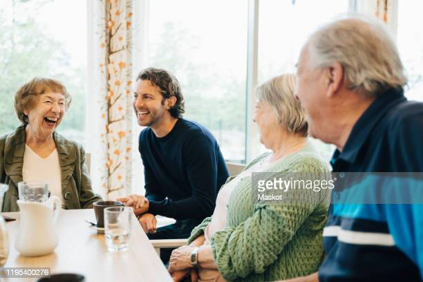 smiling man visiting his grandmother and her friends at retirement home - visit stock pictures, royalty-free photos & images