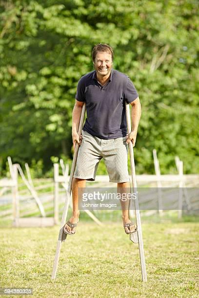 Smiling man walking on stilts
