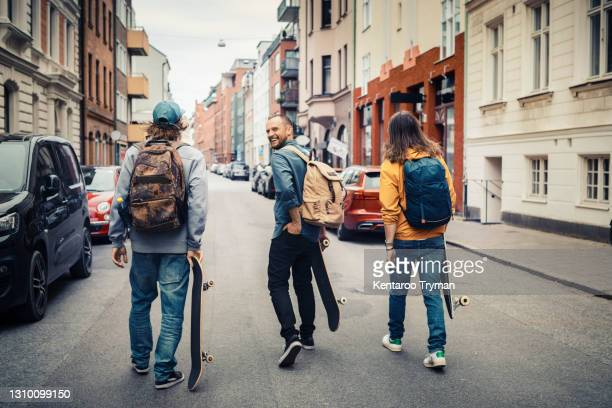 smiling man walking with male friends in city - looking over shoulder stock pictures, royalty-free photos & images
